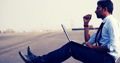 Geschäftsmann auf der Straße mit einem Laptop.