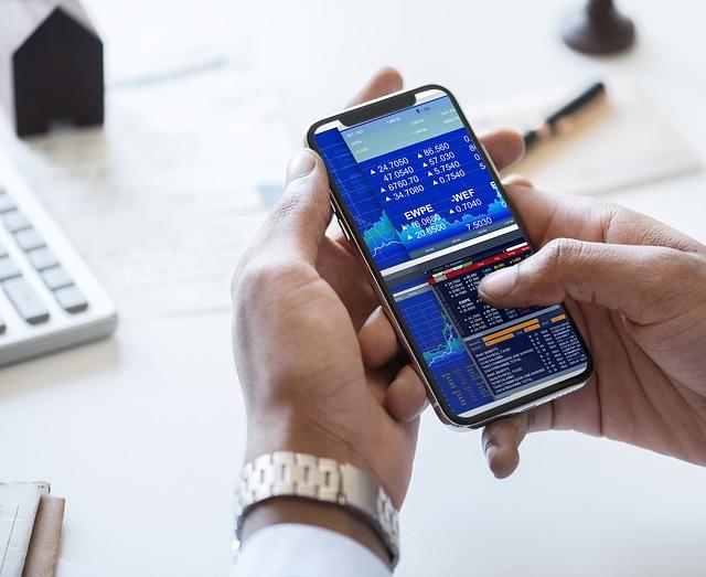 Mann checkt die Kurse von Aktien auf dem Smartphone.