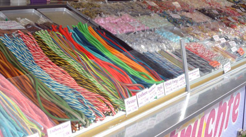 Beim Dom sind lange Süßigkeitenstangen beliebt um sie beim Dombummeln nebenbei zu knabbern